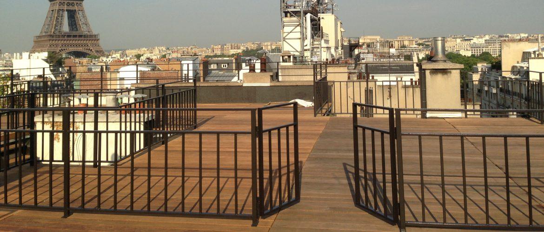Terrasse typiquement parisienne avec garde-corps laquée noir et parquet chêne
